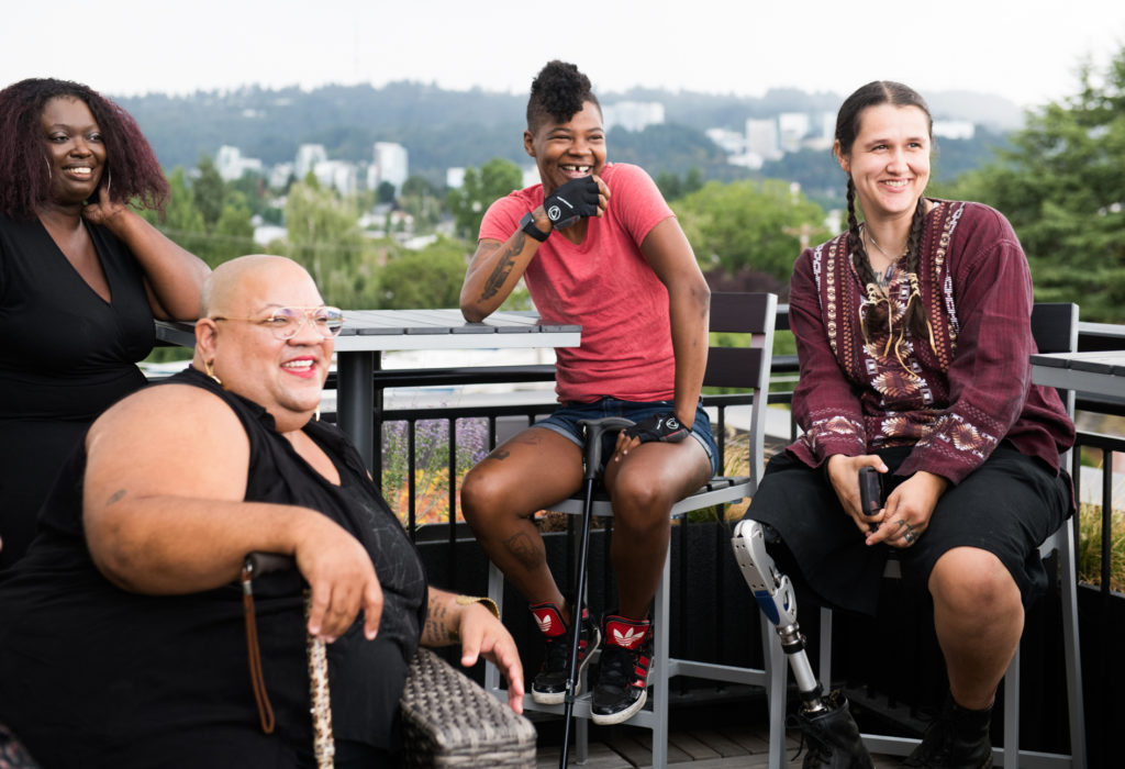 Four disabled people of color with canes and prosthetic legs laugh while chatting. They are on a rooftop deck, in chairs of various height, with greenery and city high-rises in the background.